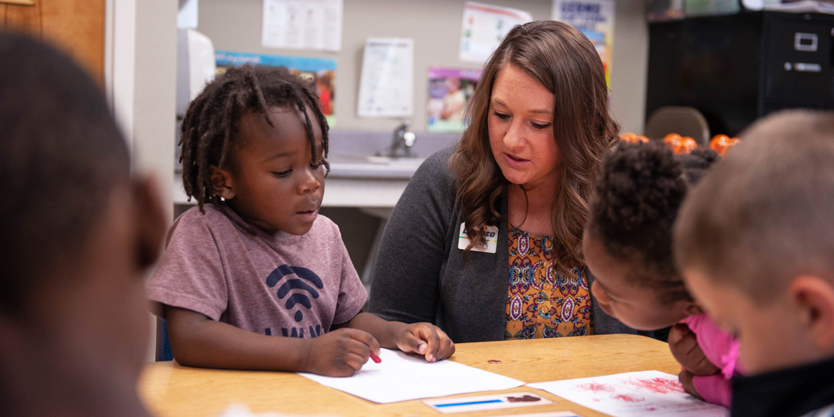 Dupaco Helping Student During A Financial Literacy Lesson At Tri-County Head Start In Waterloo, Iowa.