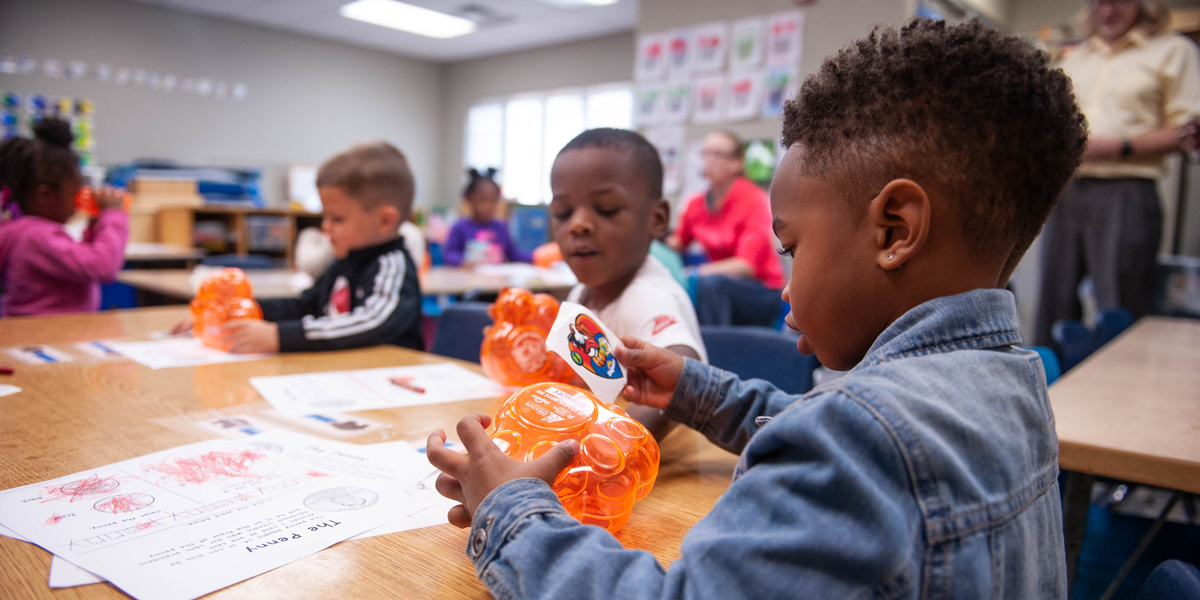 Tri-County Head Start students check out their new piggy banks.