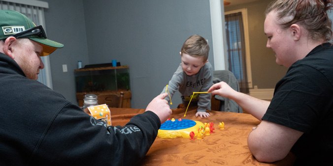 Dupaco member Ryan Bubenyak plays a game with his family at his new home.