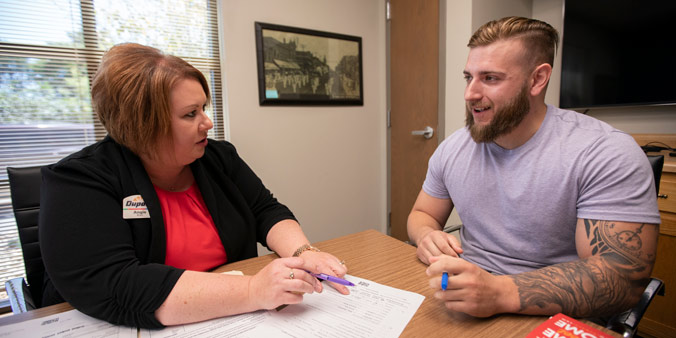 Dupaco's Angie Ries Helps Member Jon Sodawasser Sign Closing Papers On The Purchase Of His First Home Aug 16 At Dupaco's Branch In Dyersville, Iowa. (M. Burley Photo)